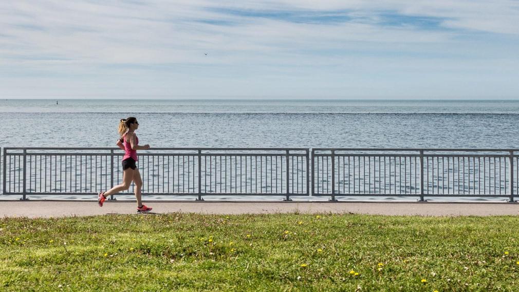 Une femme court sur le bord de l'eau