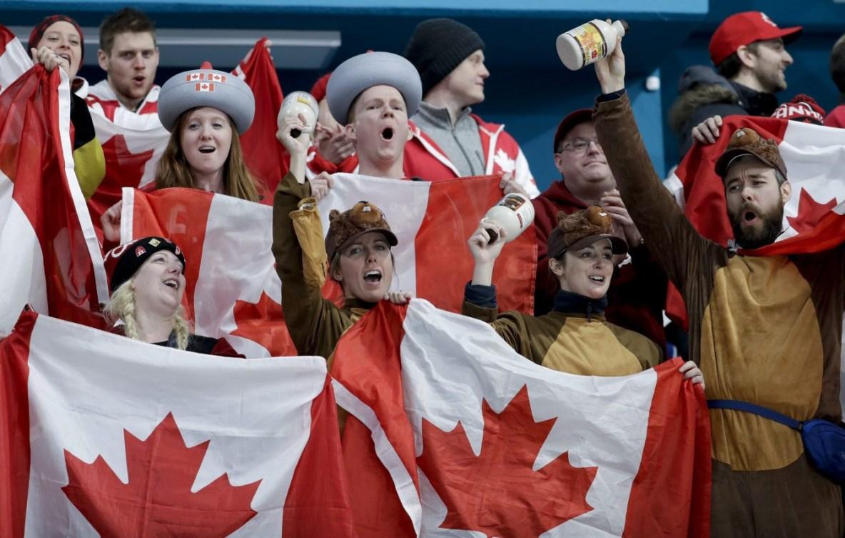 Des fans dans les estrades lèvent des drapeaux du Canada