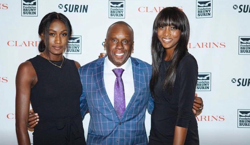 Bruny Surin pose, entouré de ses deux filles
