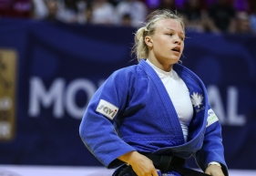 Une judoka resserre sa ceinture noire lors d'un match de judo.