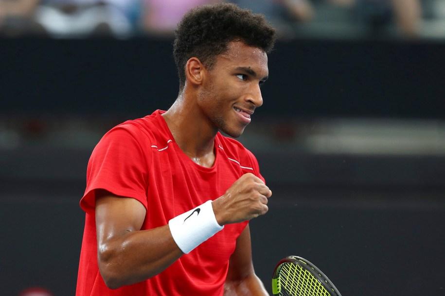 Un joueur serre le poing pour célébrer un point lors d'un match de tennis.