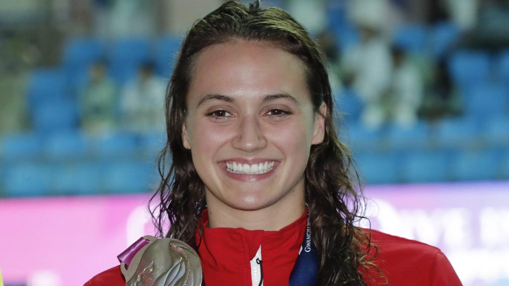 Kylie Masse sourit et montre sa médaille