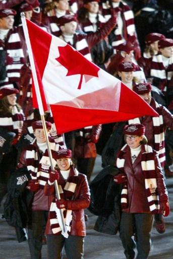 Une Canadienne porte le drapeau devant la délégation canadienne à la Cérémonie d'ouverture aux Jeux olympiques de Salt Lake City 2002