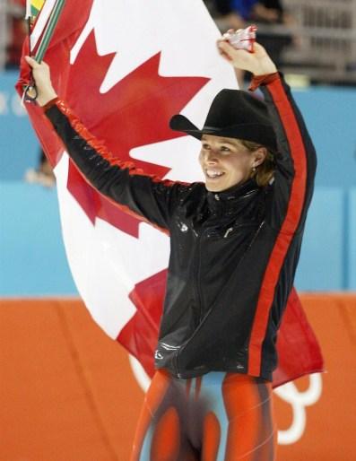 Une patineuse de vitesse célèbre sa victoire en bradissant le drapeau canadien et en portant un chapeau de cowboy