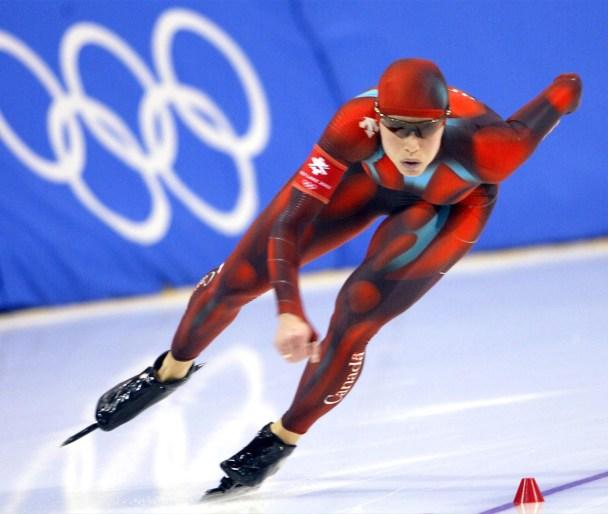 Une patineuse fait des croisés dans la courbe d'un anneau olympique