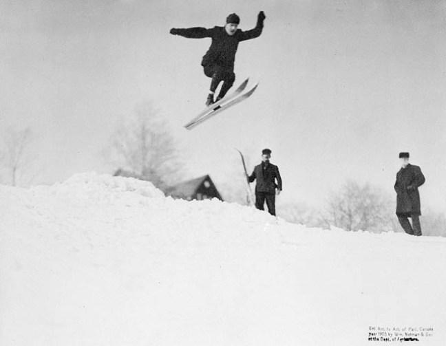 un skieur des années 1900 effectue un saut depuis une butte de neige