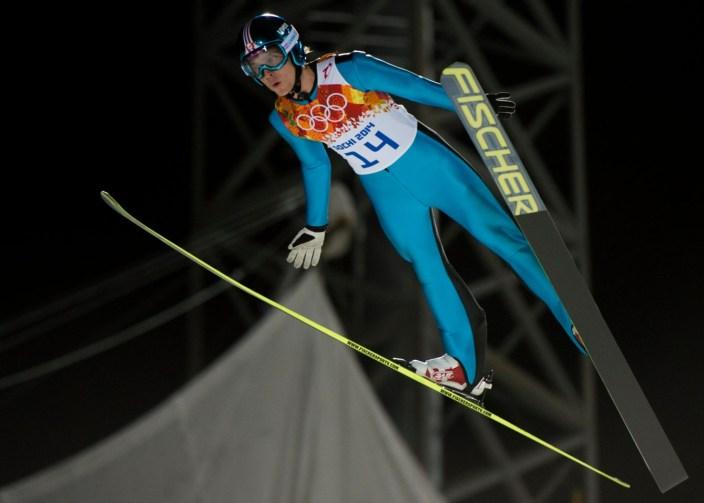 Un skieur effectue un saut depuis le grand tremplin aux Jeux olympiques de Sotchi 2014
