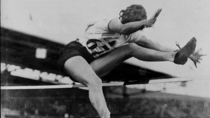 Une sauteuse en hauteur passe par dessus la barre en effectuant un coup de ciseaux aux Jeux olympiques de 1928