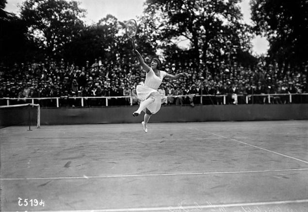 Une joueuse de tennis des années 1920 dans une grande robe blanche saute pour atteindre la balle