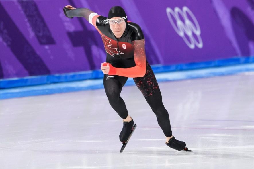 Un patineur de vitesse prend le départ sur un anneau olympique