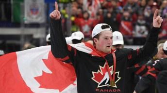 Un joueur de hockey célèbre avec le drapeau canadien porté en cape.