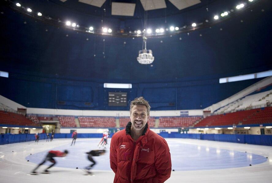 Un entraîneur pose devant une glace de patinage de vitesse sur courte piste