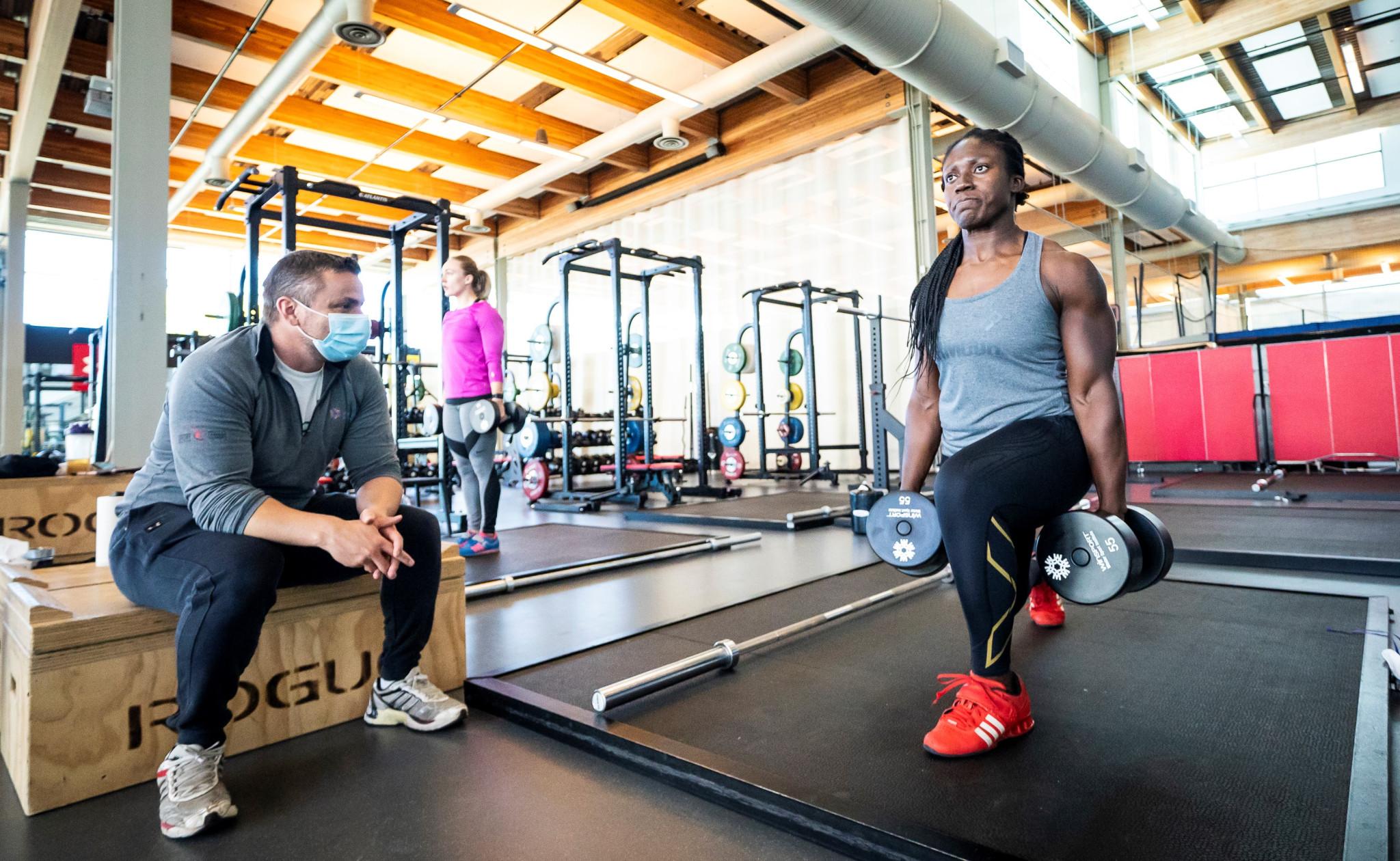 Cynthia Appiah s'entraîne avec des poids libres au gym.
