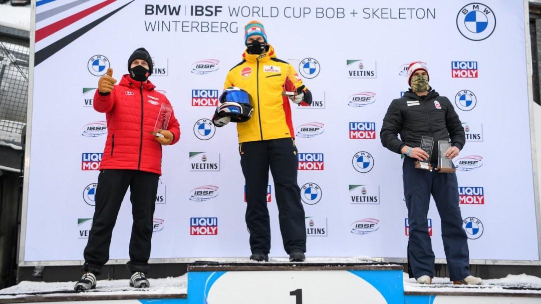 Justin Kripps sur la deuxième marche du podium aux côtés de Francesco Friedrich et de Benjamin Maier