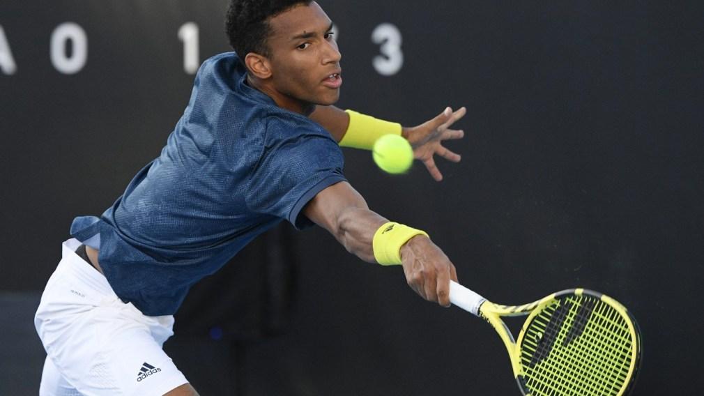 Félix Auger-Aliassime frappe la balle de tennis en jouant contre le Japonais Yuicha Sugita à Melbourne, en Australie.