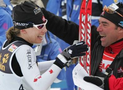 Une skieuse et un technicien célàbrent une victoire