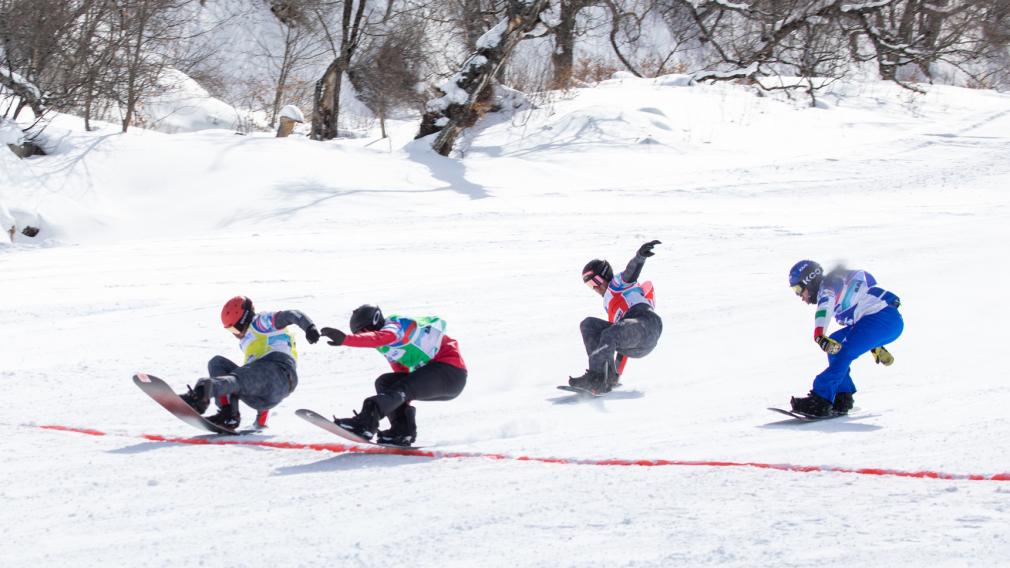 Quatre athlètes de snowboard cross s'apprêtent à franchir la ligne d'arrivée dans une finale très serrée.