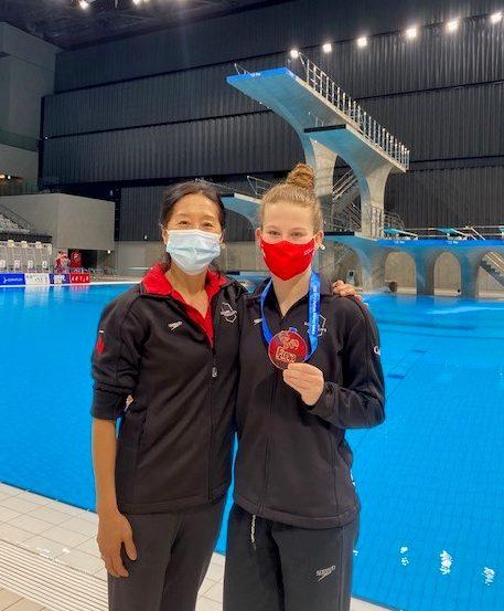 Caeli McKay avec sa médaille de bronze au cou en compagnie de son entraîneure Yihua Li.