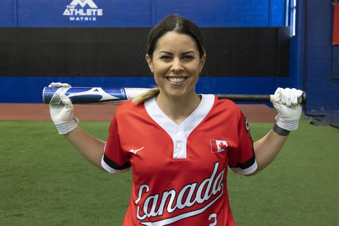 Une joueuse de softball sourit à la Canada