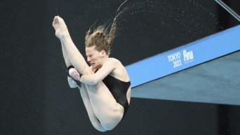Une plongeuse en position carpé plonge de la plateforme de 10 m.