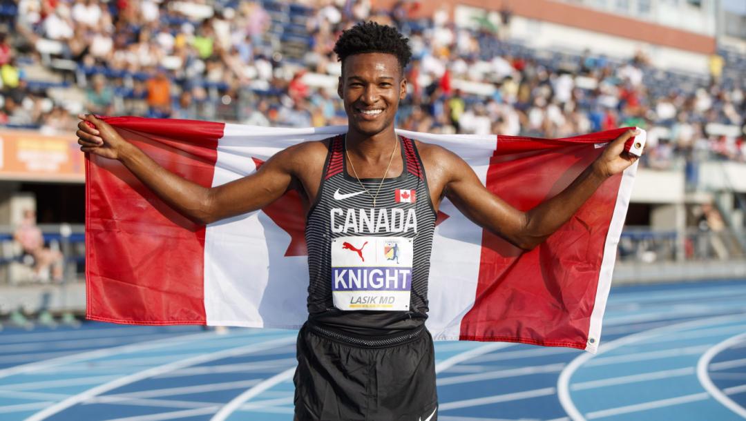 Justyn Knight pose avec le drapeau canadien.