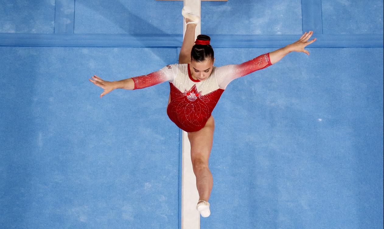 Une gymnaste en plein saut sur la poutre
