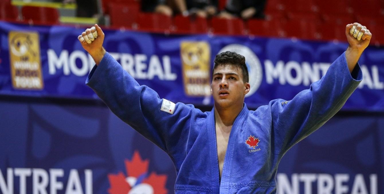 Un judoka lève les bras en signe de victoire