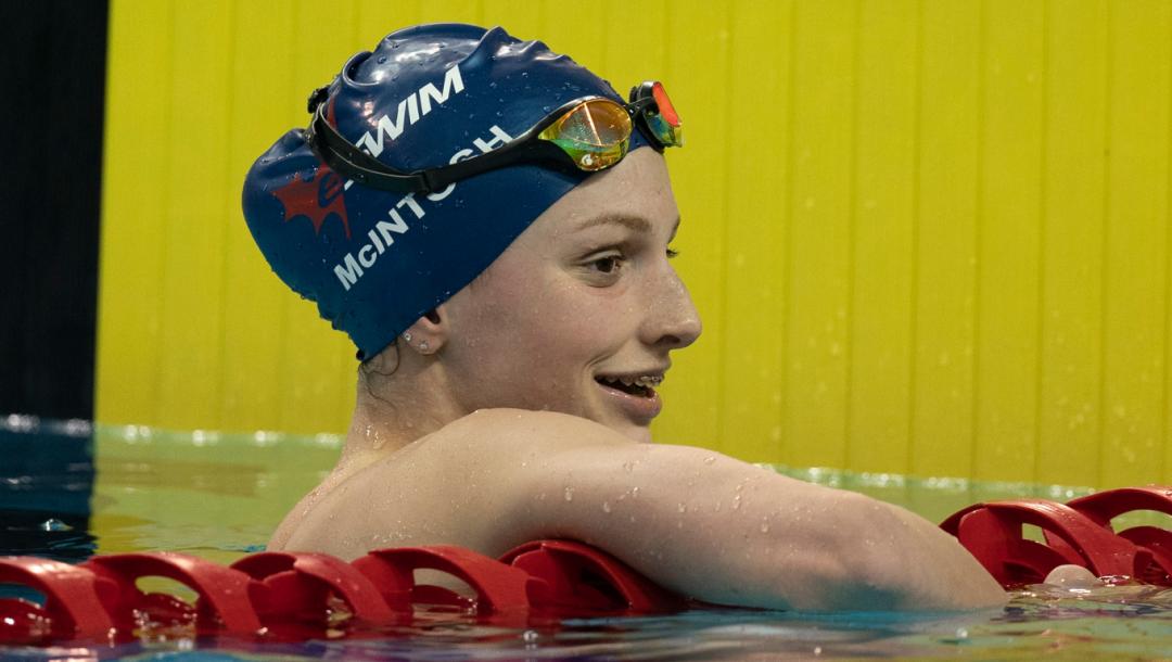 Une nageuse sourit à la fin de sa course