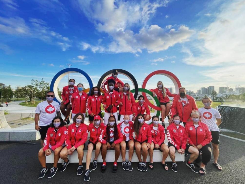 L'équipe féminine de rugby à sept pose devant les anneaux olympique au Village olympique.