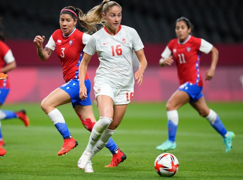 La joueuse canadienne Janine Beckie contrôle le ballon à ses pieds, avec deux joueuses chiliennes en arrière-plan.