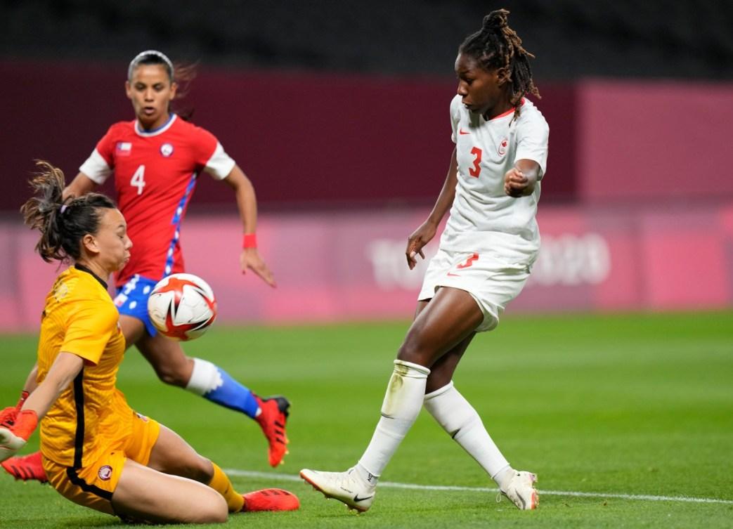 Kadeisha Buchanan du Canada frappe le ballon dans la poitrine du gardien chilien alors qu'elle glisse pour le bloquer.