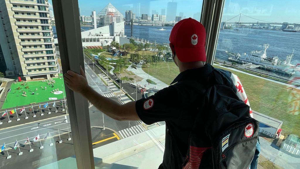 Un athlète regarde la vue du village olympique