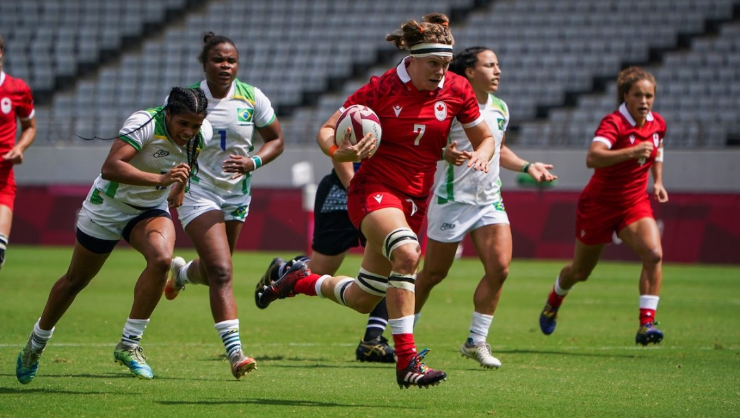 Une joueuse de rugby porte le ballon.