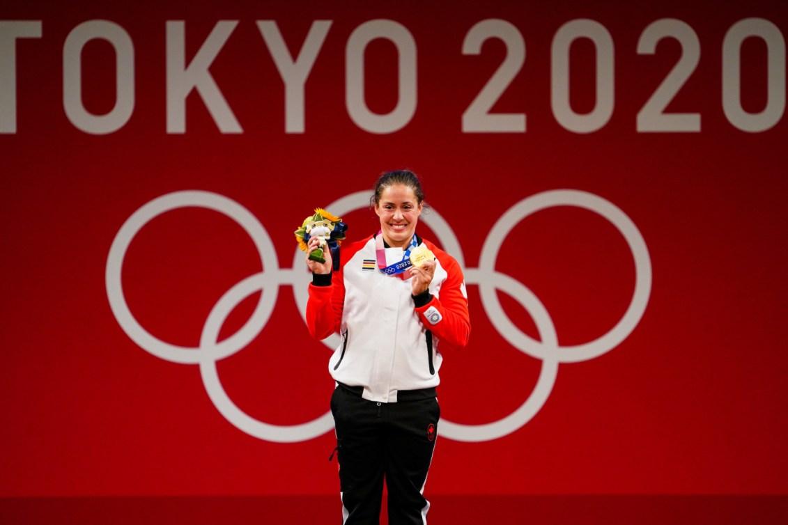 Une haltérophile canadienne montre sa médaille d'or sur le podium