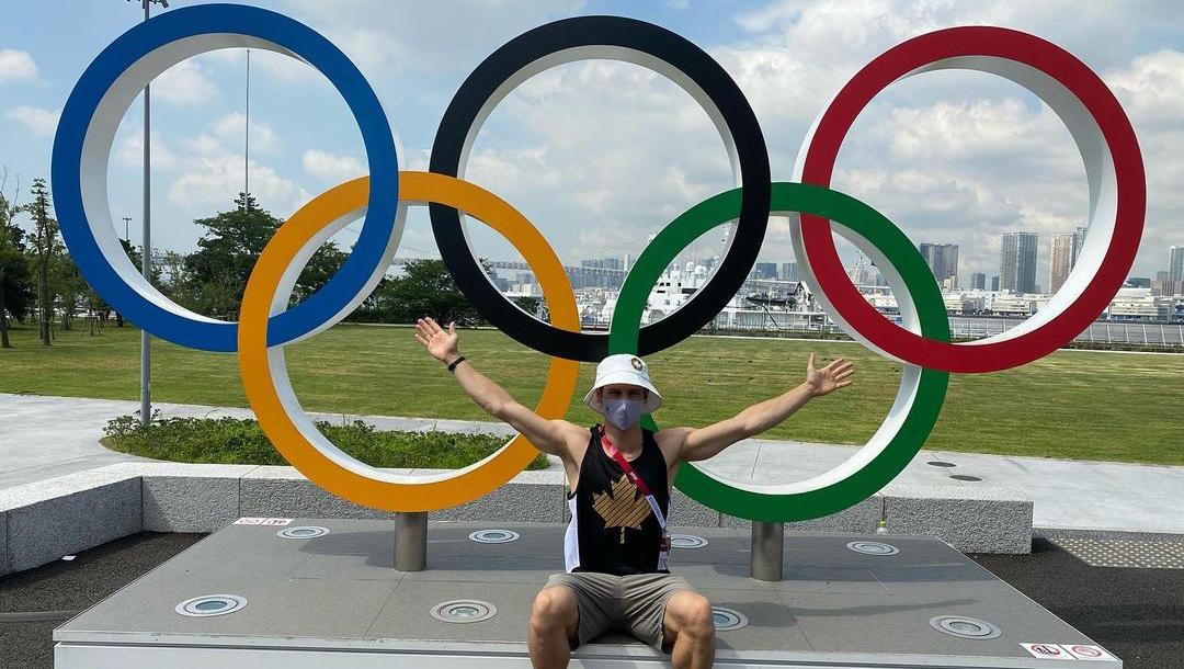 Vincent Riendeau pose devant les anneaux olympique au village des athlètes.
