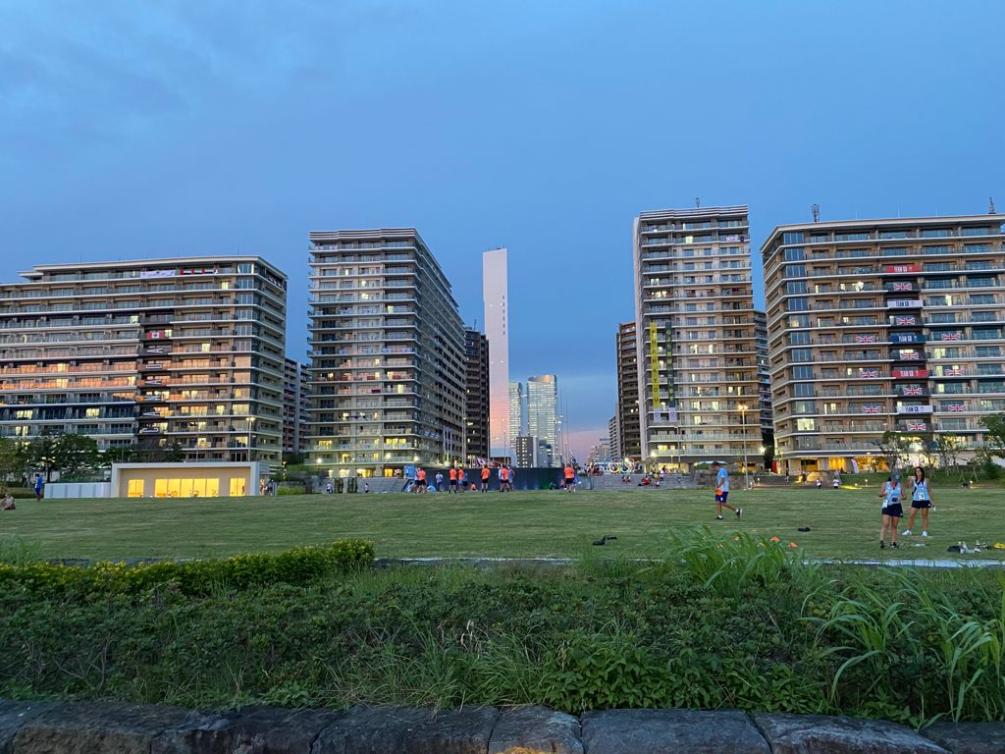 Des athlètes s'entraînent dans un parc du Village olympique au coucher du soleil.