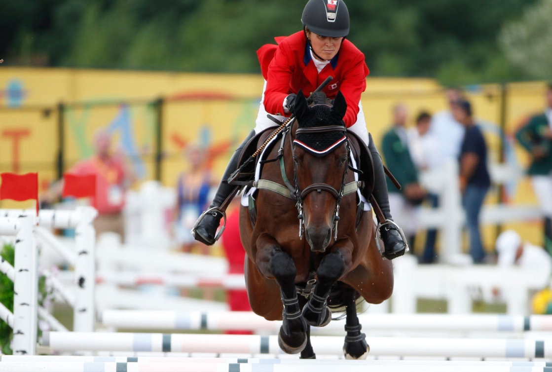 Une athlète sur son cheval saute une haie