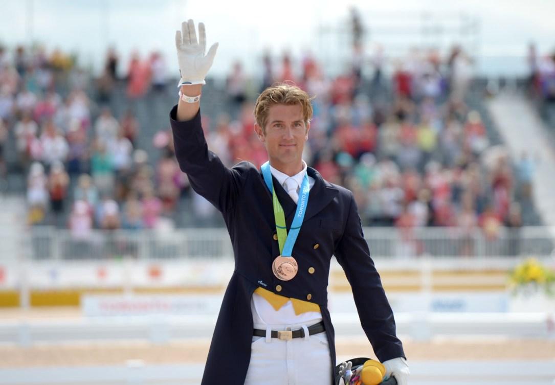 Un athlète de sports équestres salue la foule avec sa médaille