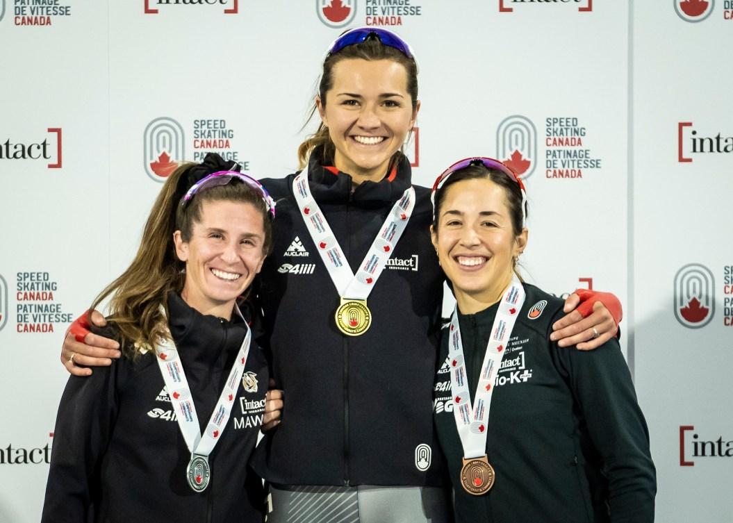 Trois patineuses avec leur médailles autour du cou.