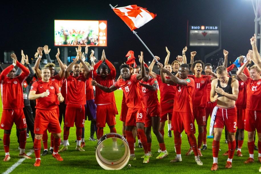 Les joueurs de soccer d'Équipe Canada célèbrent sur le terrain en posant pour la caméra.