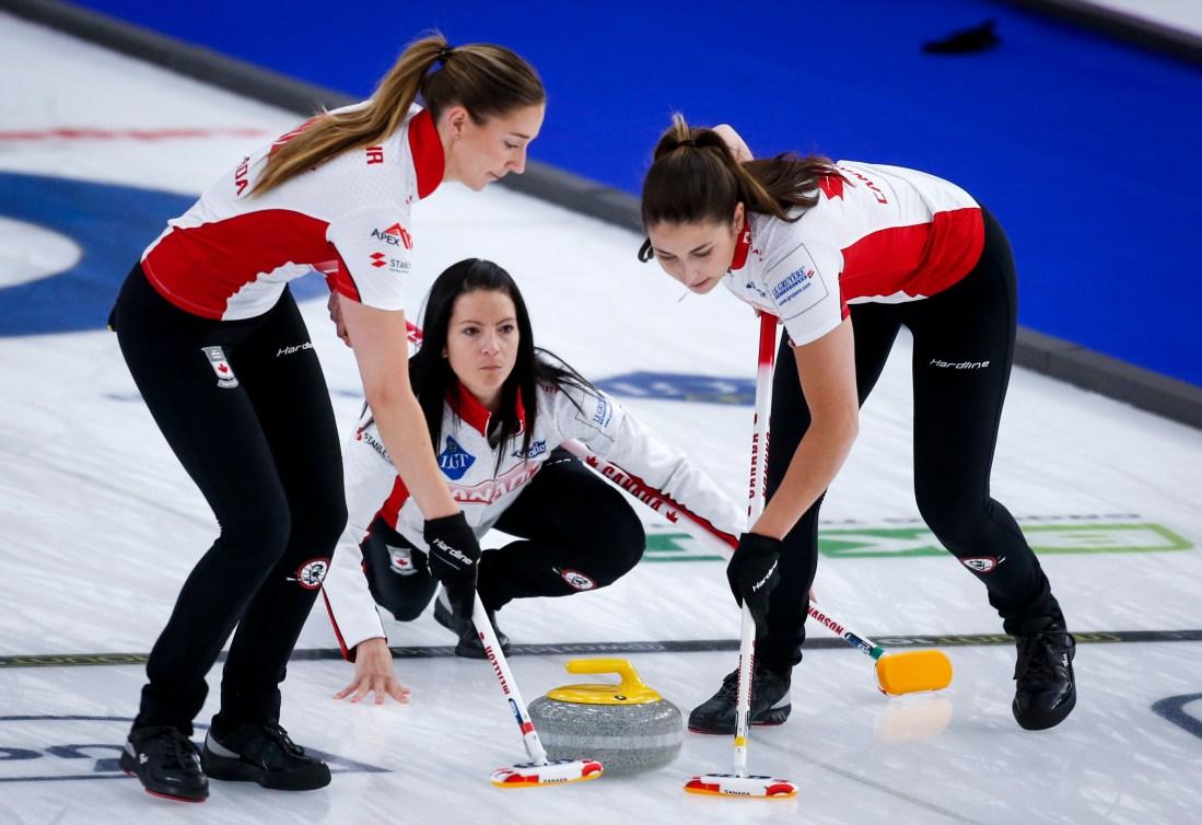 Trois joueuses de curling en action