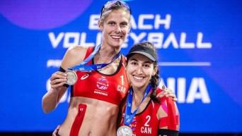 Deux joueuse de volleyball de plage avec des chandails à manches longues s'enlacent avec leur médaille d'argent au cou en souriant et en regardant vers la caméra.